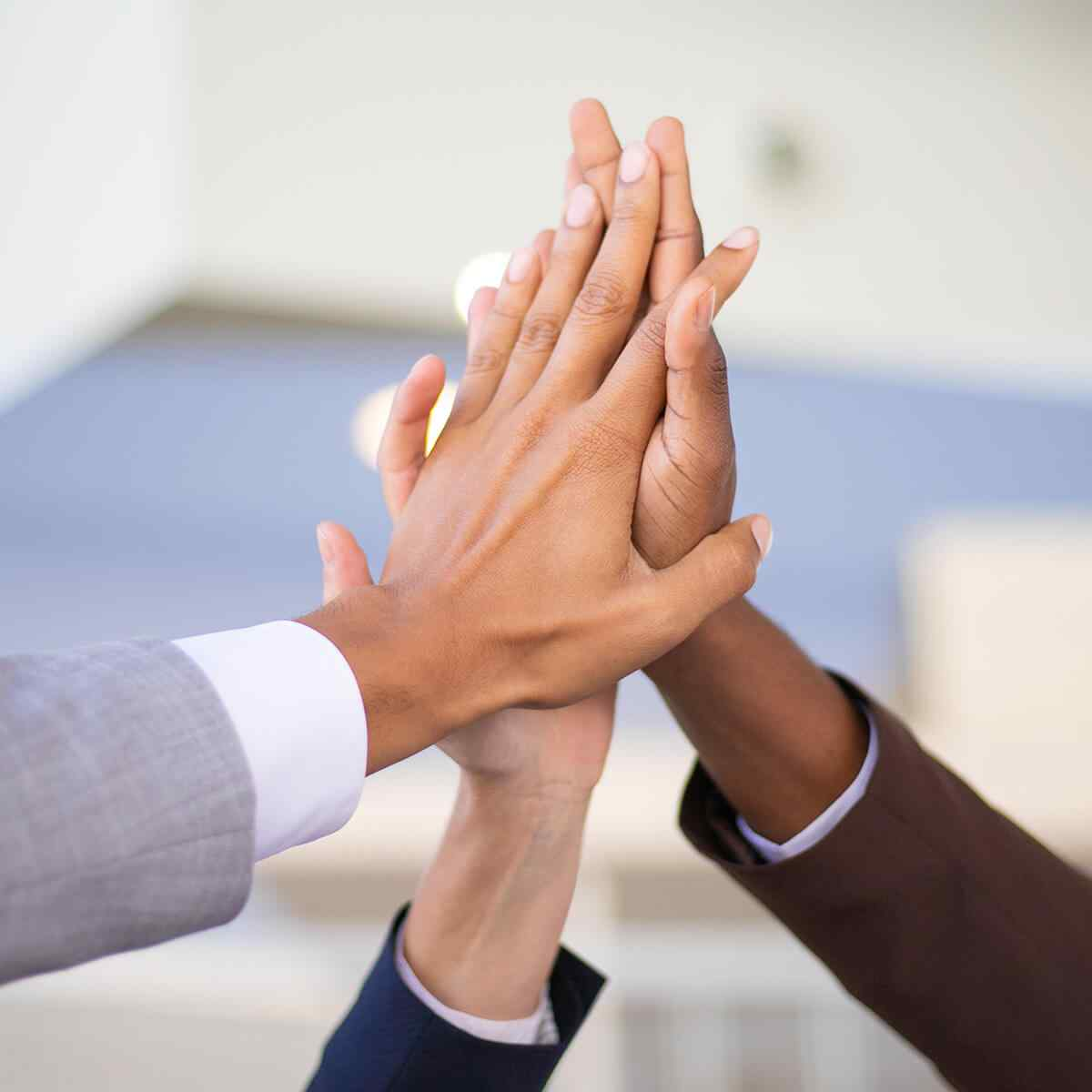 Business colleagues celebrating success and joining hands. Multiethnic group of man and women giving high five to each other. Achievement concept